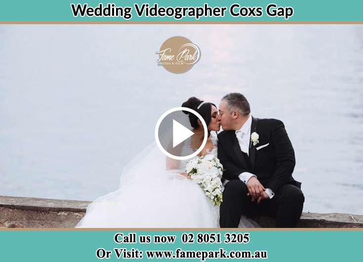 The newlyweds kissing near the shore Coxs Gap NSW 2333