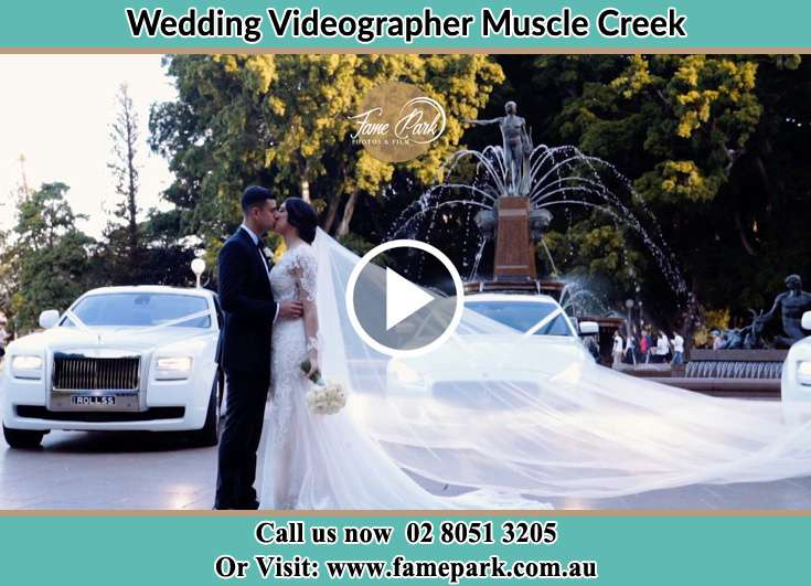 The newlyweds kissing near the wdding car Muscle Creek NSW 2333