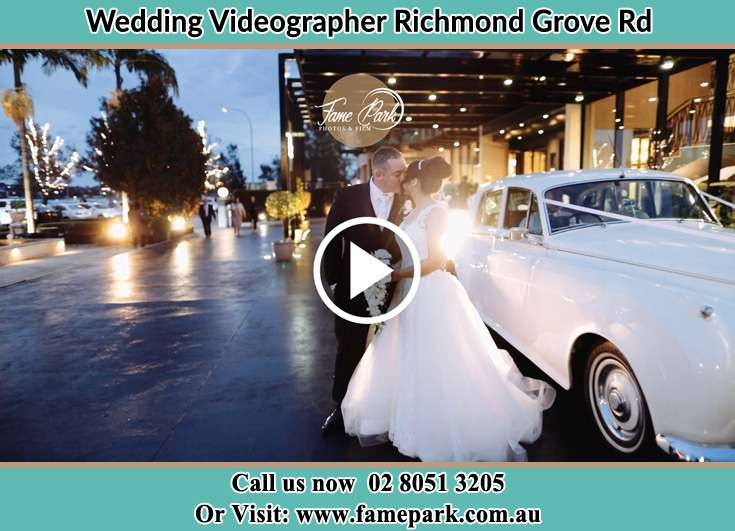 The newlyweds kissing near the wedding car Richmond Grove Rd NSW 2333